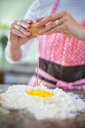 Mature woman cracking egg onto flour, mid section - ISF02483