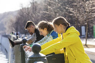 Friends doing stretching exercise on railing in the city - WPEF00301