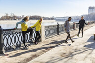 Friends exercising on waterfront promenade in the city - WPEF00310