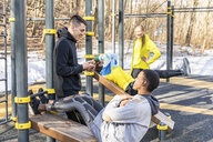 Friends exercising at fitness equipment in a park - WPEF00322