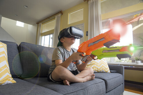 Young boy sitting cross legged on sofa, wearing virtual reality headset, holding laser guns, digital composite - ISF02522