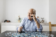 Happy senior man using smartphone while doing a puzzle at home - JRFF01678