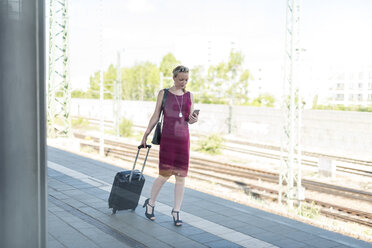 Mature businesswoman with smartphone and suitcase walking at platform - DIGF04471