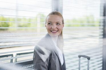 Portrait of smiling mature businesswoman waiting at platform - DIGF04474