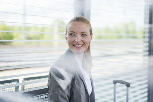 Portrait of smiling mature businesswoman waiting at platform - DIGF04474