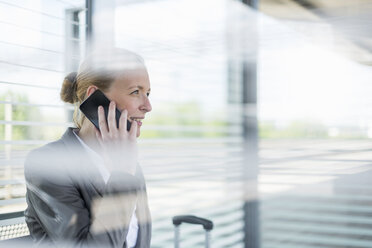 Portrait of mature businesswoman on the phone waiting at platform - DIGF04477