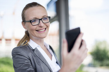 Portrait of smiling businesswoman looking at cell phone - DIGF04486