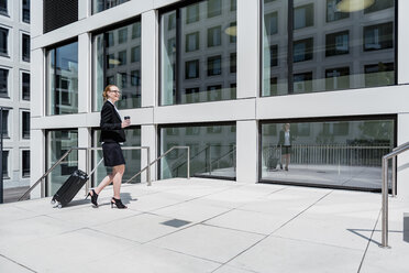Smiling businesswoman with suitcase and coffee to go walking in front of office building - DIGF04489
