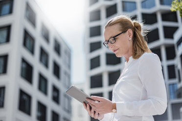 Portrait of businesswoman using tablet outdoors - DIGF04495