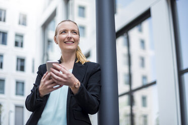 Portrait of smiling businesswoman with cell phone waiting - DIGF04498