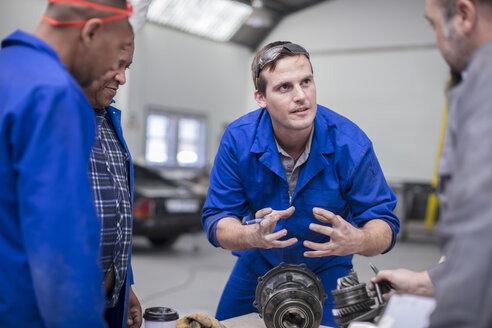 Car mechanic team discussing car part in repair garage - ISF02844