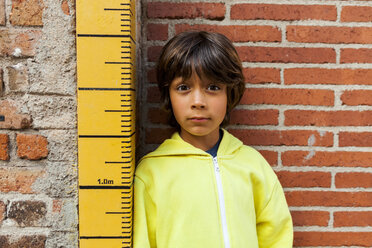 Portrait of sceptical boy leaning against yardstick - VABF01613
