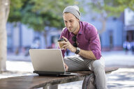 Young man outdoors, sitting on bench, using laptop, holding takeaway coffee cup - ISF02861