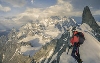 Mountain climber on the Rochefort Ridge looking at Mont Blanc, Courmayeur, Aosta Valley, Italy, Europe - ISF03169