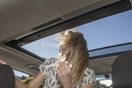 Young woman in car, looking out of open sun roof - ISF03202