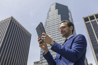 Smiling young businessman looking at digital tablet by New York skyscrapers, USA - ISF03253