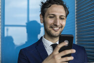 Smiling young businessman in city looking at smartphone - ISF03259