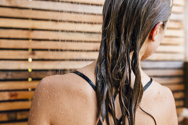 Young woman using outdoor shower, rear view - ISF03304