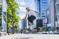 Skateboarder on street in town centre, Montreal, Quebec, Canada - ISF03328