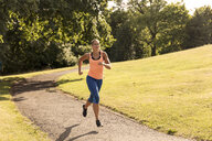 Young female runner running along park path - ISF03481