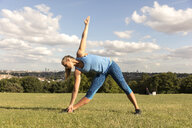 Young woman practicing yoga in park, standing and bending over sideways - ISF03484
