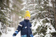 Portrait of boy in yellow knit hat walking in snow covered forest - ISF03508