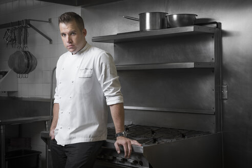 Portrait of pastry chef leaning against hob in kitchen - ISF03556