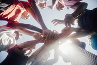 Low angle view of schoolgirl soccer team in circle with hands together - ISF03565