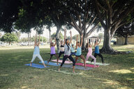 Schoolgirls practicing yoga warrior one pose on school sports field - ISF03568
