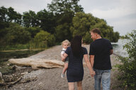 Rear view of couple strolling on beach with male toddler son, Lake Ontario, Canada - ISF03631