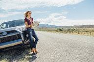 Woman with map leaning against car - ISF03670