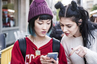 Two young stylish women looking at smartphone on city street - ISF03721