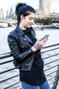 Young woman looking at smartphone on millennium footbridge, London, UK - ISF03727