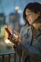 Woman texting on smartphone, New York, United States, North America - ISF03733