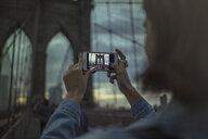 Woman photographing Brooklyn bridge using smartphone, New York, United States, North America - ISF03736