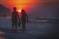 Siblings paddling in sea at sunset, North Myrtle Beach, South Carolina, United States - ISF03793