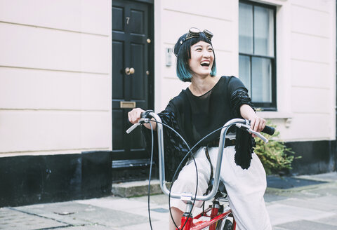 Young stylish woman cycling retro bicycle on street - ISF03820