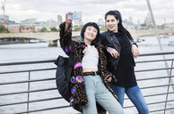 Two young stylish women taking smartphone selfie on millennium footbridge, London, UK - ISF03826