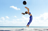 Young woman training, jumping mid air with exercise ball on beach - ISF03904