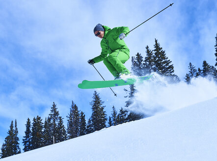 Man jumping while skiing down snow covered mountainside, Aspen, Colorado, USA - ISF04039