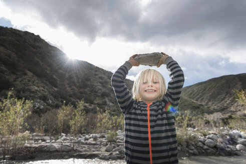 Portrait of cute boy holding up rock from riverbed - ISF04201