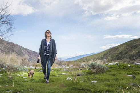 Mature woman walking dog in valley landscape - ISF04204