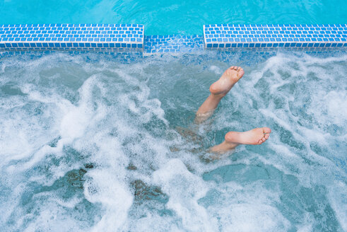 Overhead view of diving boy's feet in splashing outdoor swimming pool - ISF04207