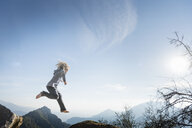 Boy jumping, blue sky in background, Sequoia National Park, California, US - ISF04225