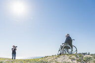 Senior woman photographing husband in wheelchair on dunes, Playa del Ray, California, USA - ISF04234