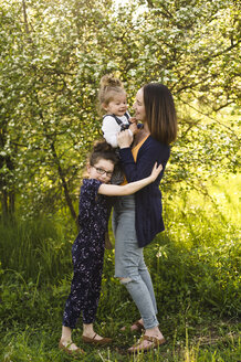 Mid adult woman and daughters in field with blossoming trees - ISF04384