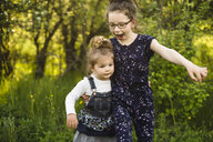 Girl and little sister playing in field with trees - ISF04387