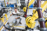 Young male engineer testing machinery in engineering factory - ISF04396