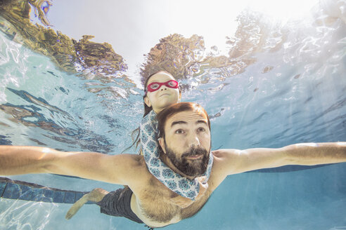 Underwater view of mature man swimming with daughter on piggy back - ISF04408