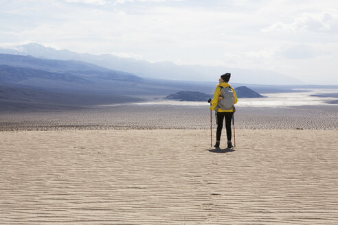 Trekker taking in sights, Death Valley National Park, California, US - ISF04441